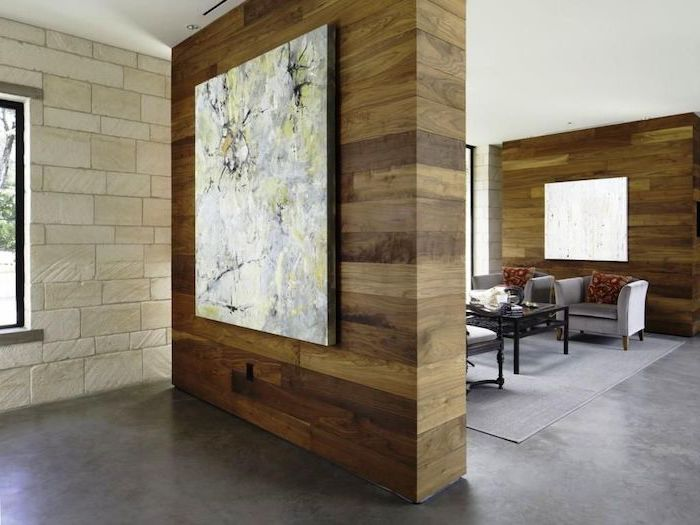 decorative room dividers, made of wood, abstract art, stone wall, cement floor, grey armchairs