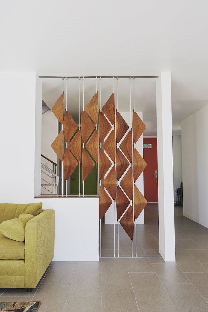 wooden triangles, arranged together, decorative room dividers, green sofa, tiled floor