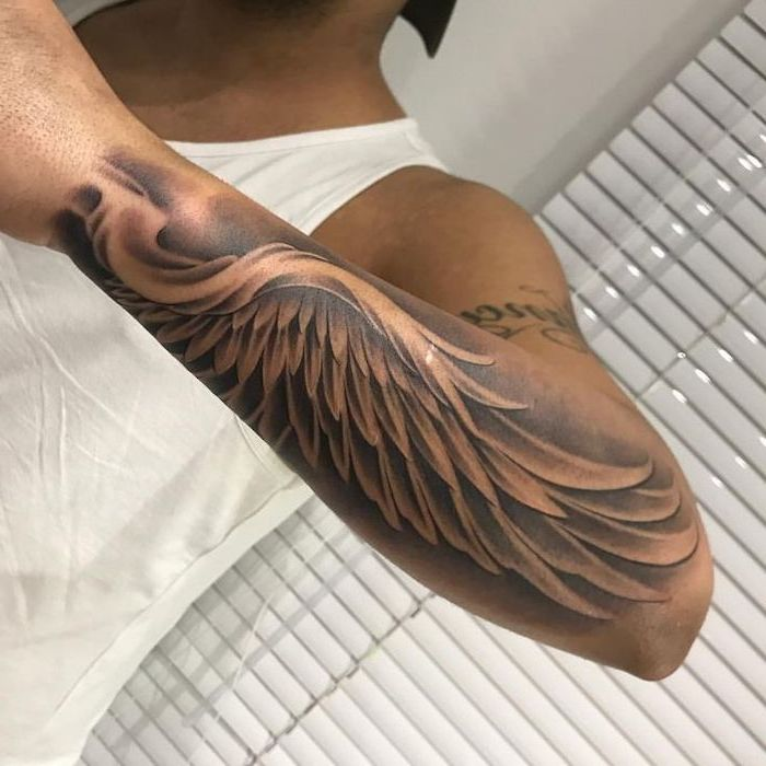 angel wings tattoo, arm tattoo, man with white top, white blinds in the background