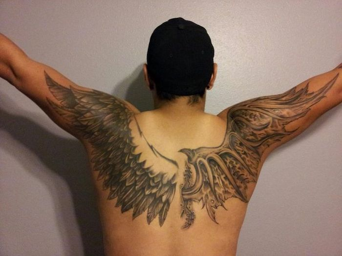 wings chest tattoo, man with black hair, one angel wing, one devil wing, white background