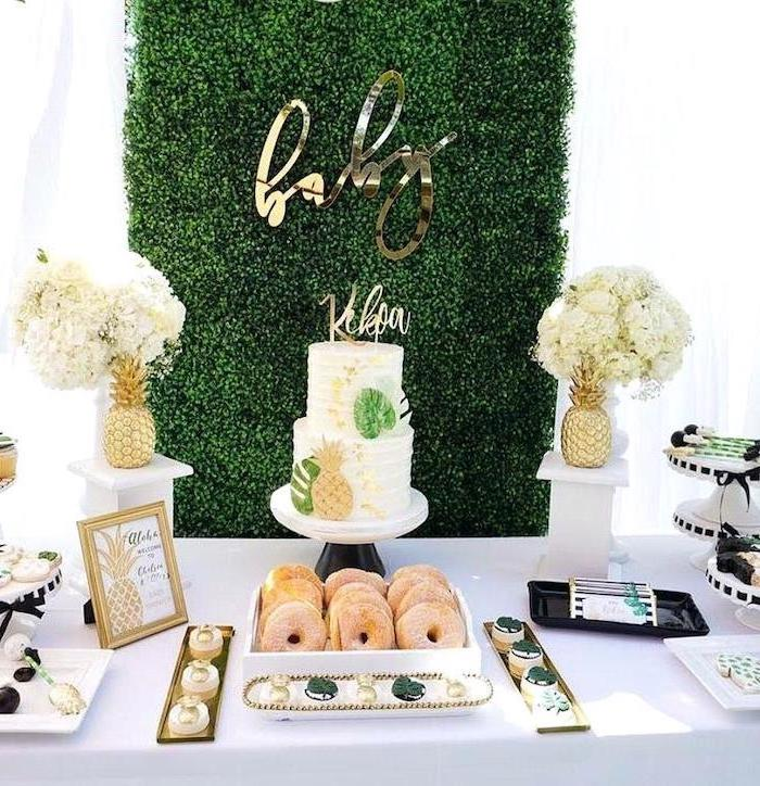 greenery wall, two tier cake, donuts and cupcakes, flower bouquets, baby shower decoration ideas, pineapples theme