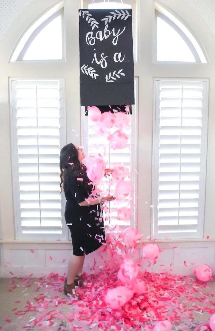 baby is a, black box, full of pink balloons, pink confetti, gender reveal party, woman standing underneath