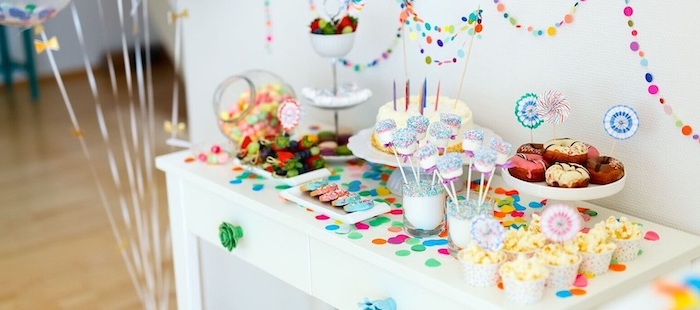 colorful decorations, on a white wooden table, cake and donuts, cake pops, popcorn in a cup, baby shower ideas for girls