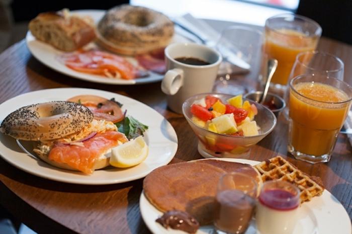 halved bagels, salmon and tomatoes inside, brunch menu, orange juice and coffee, fruit bowl