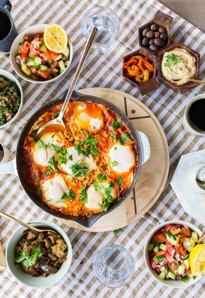 baking pan, eggs with tomato sauce, wooden board, brunch ideas, bowls of different garnish