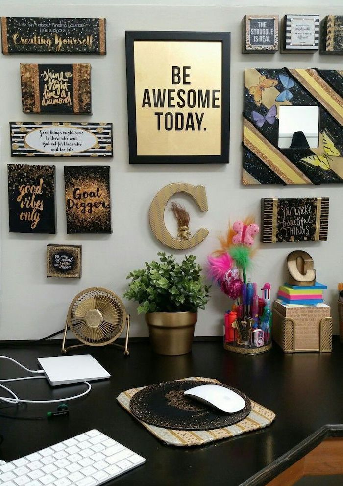 cubicle decor, framed art, hanging on the wall, black desk underneath, gold desk accessories