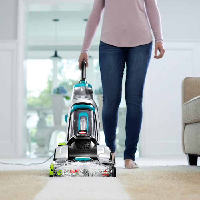 best vacuum cleaner, woman cleaning, wearing jeans, pink blouse, white carpet