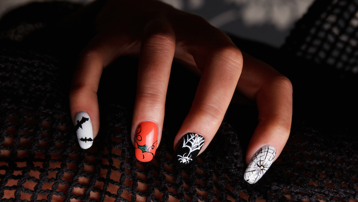 orange and black, white nail polish, black bats, spider web decorations, squoval nails, halloween nail ideas