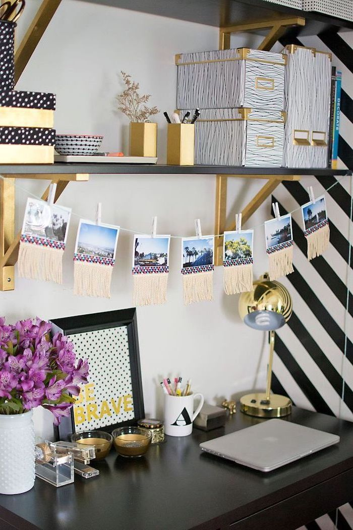 black desk, hanging photos above, wooden shelf, gold desk accessories, cubicle decor, purple flower bouquet