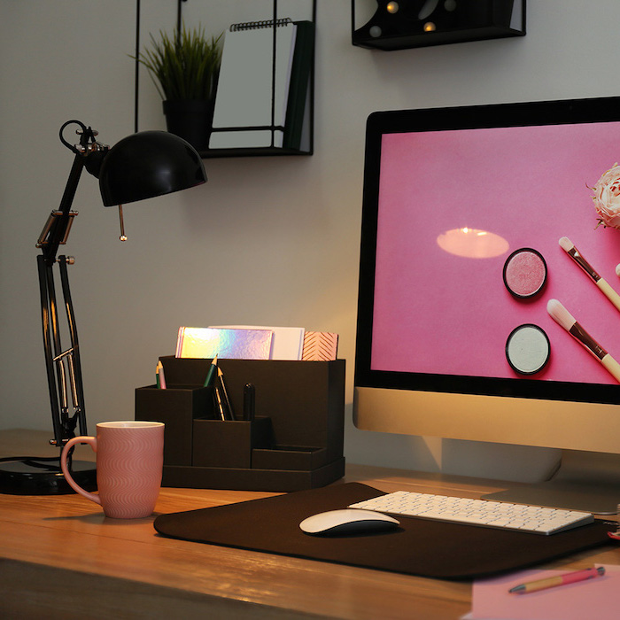 wooden desk, cubicle decor, black desk organiser, pink coffee mug, black metal shelves, desktop computer