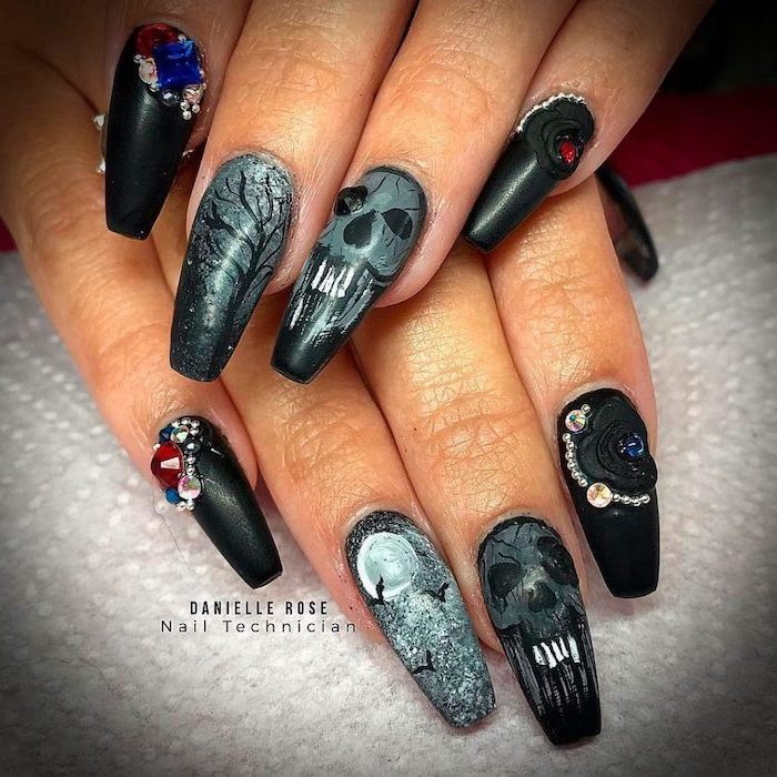 black and grey matte nail polish, halloween nails, skulls and spooky forrest decorations, red and blue rhinestones