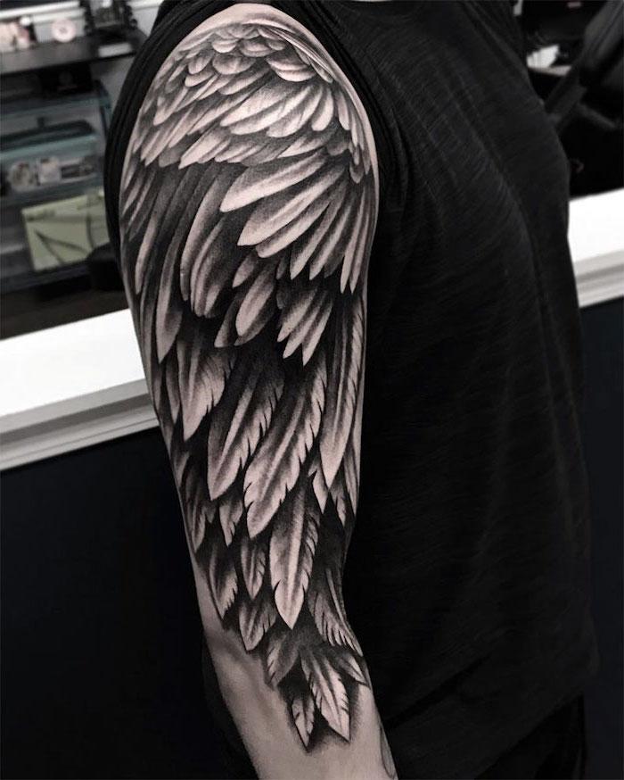 arm sleeve tattoo, small angel wings tattoo, man wearing a black top