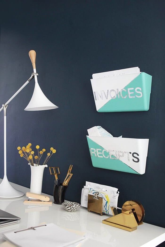 black wall, invoices and receipts folders, hanging on it, cubicle decor, white desk, gold desk accessories