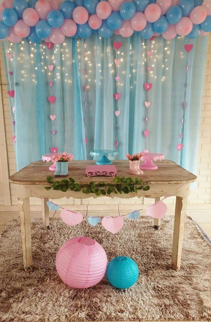 blue and pink balloons, blue tulle, fairy lights, gender reveal themes, wooden table, cake stands