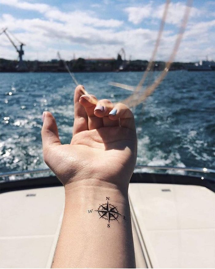sea wives, ship pier, compass tattoo meaning, wrist tattoo, white boat, cloudy sky, in the background