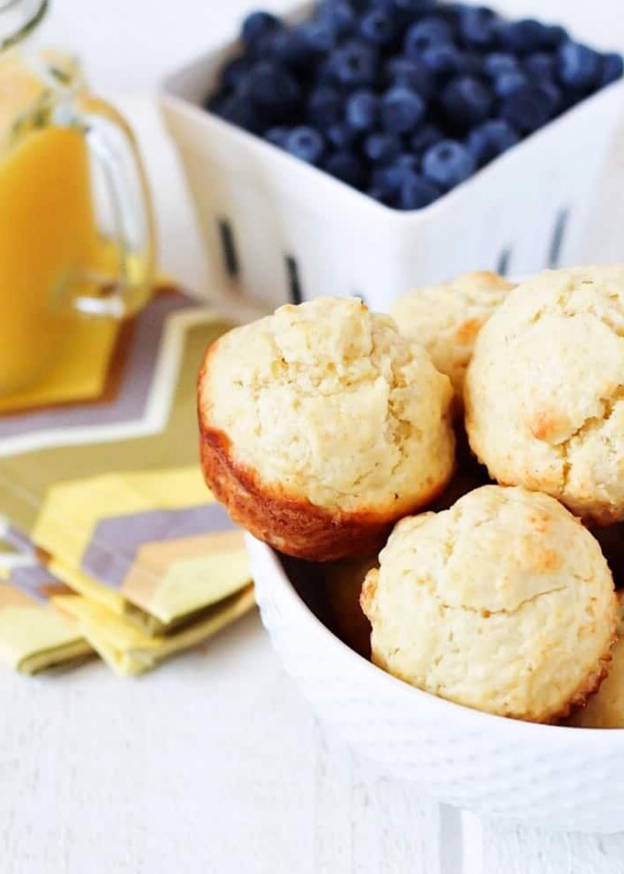 blueberries in a bowl, good breakfast ideas, white bowl, full of muffins, white wooden table