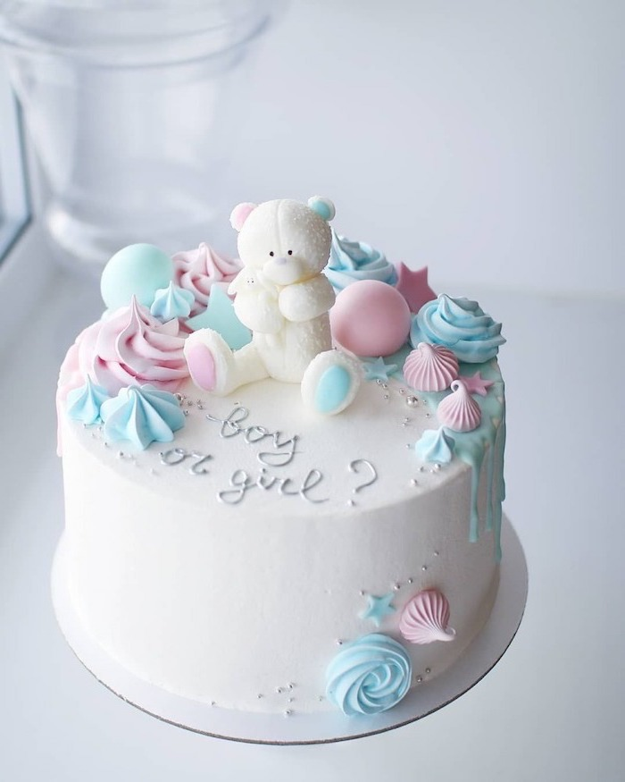 small cake, with white frosting, white teddy bear, cake topper, gender reveal games, blue and pink decorations