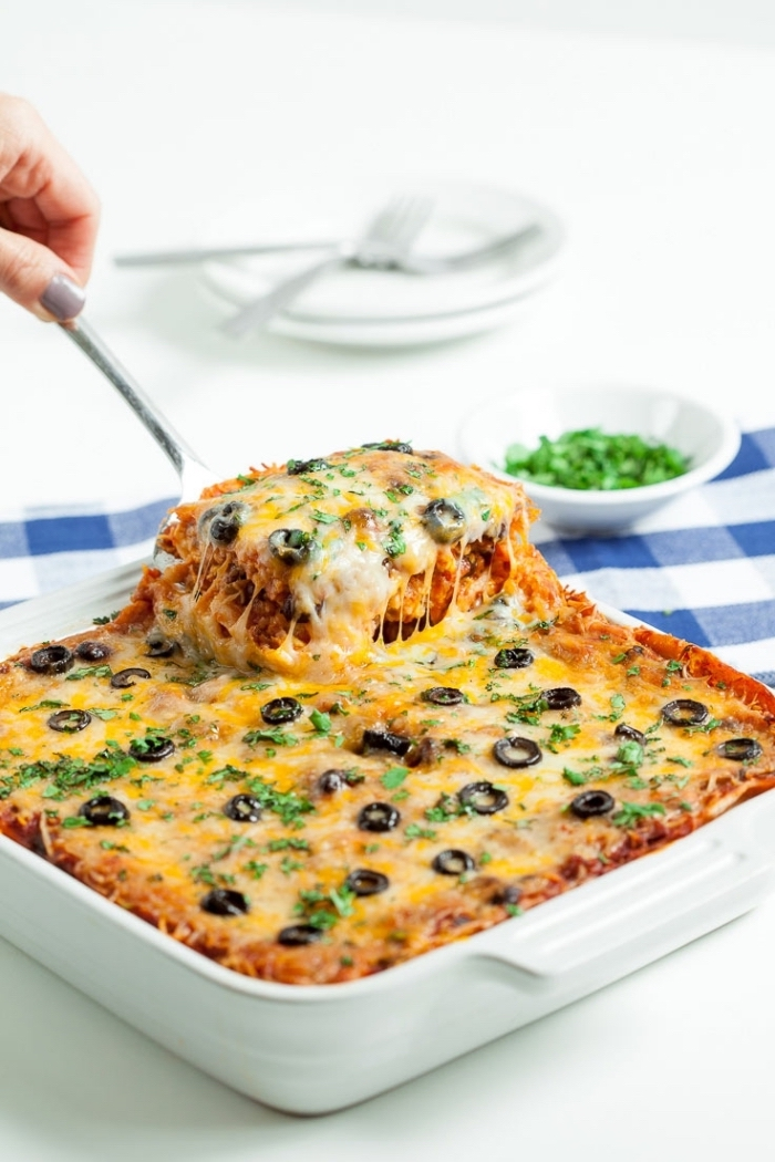 baked casserole, with olives and chives on top, breakfast food ideas, metal spatula, white table