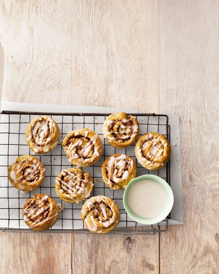 best breakfast recipes, cinnamon buns, with white frosting, on a black metal railing, wooden table