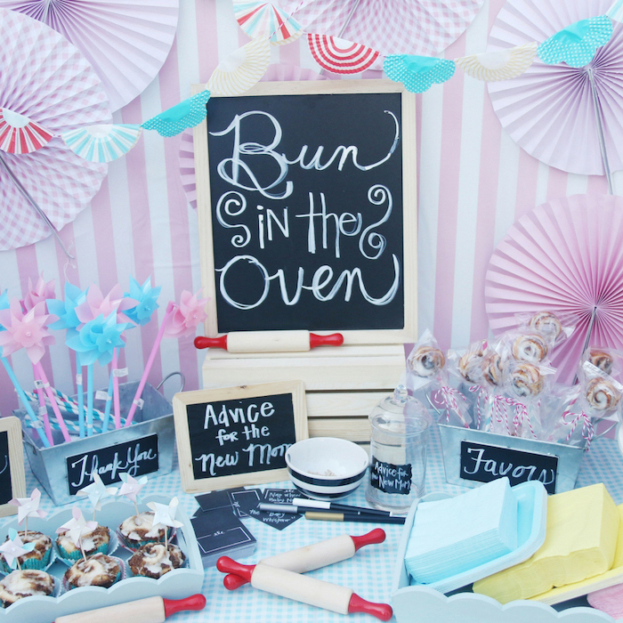 bun in the oven, black chalkboard, cinnamon buns, in a blue tray, colorful decorations, baby shower ideas