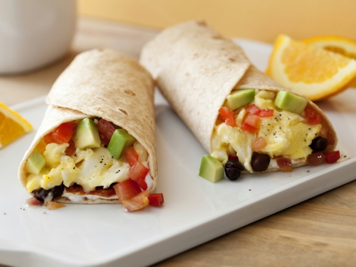 wrapped burritos, breakfast dishes, chopped avocado and tomatoes, eggs inside, on white board