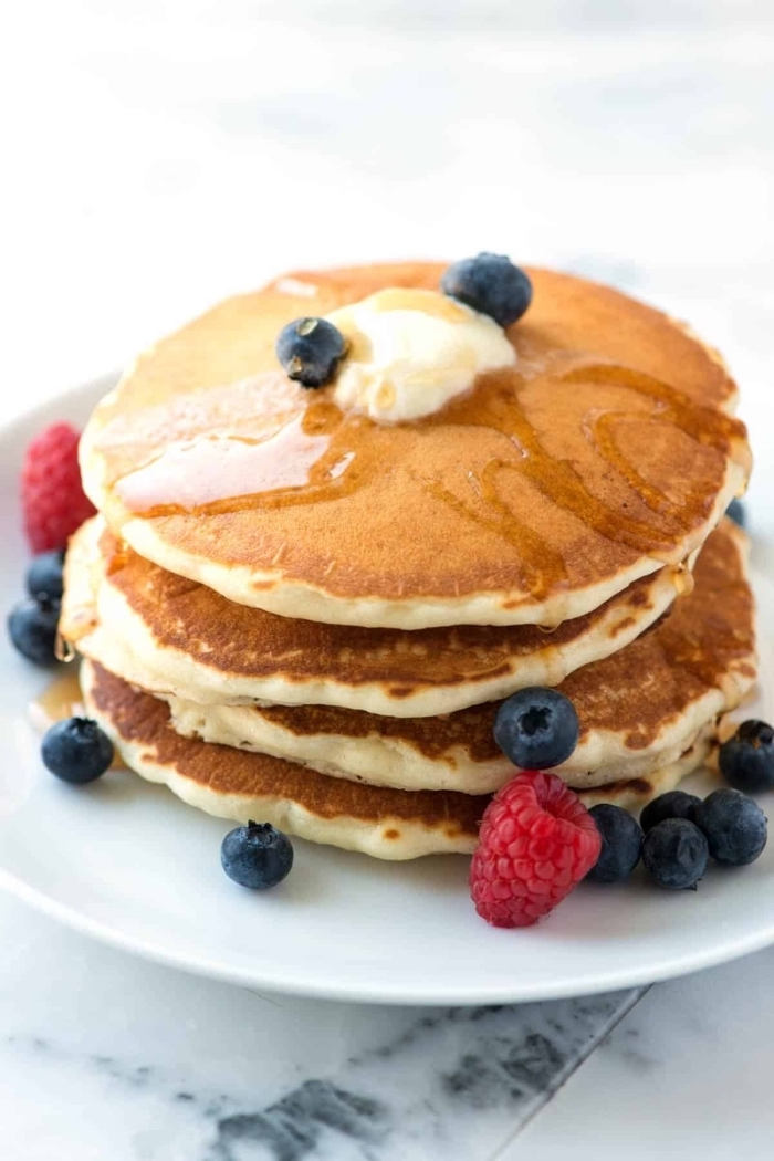 pancakes stack, butter and honey on top, blueberries and raspberries, breakfast dishes