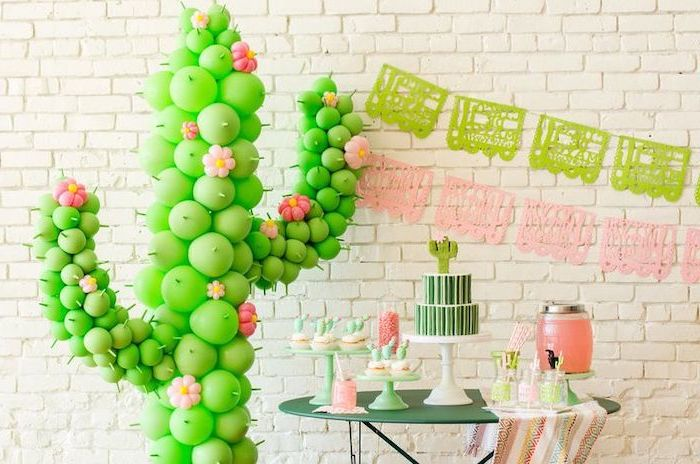 cactus made out of green balloons, green metal table, white brick wall, baby shower decorations, dessert table