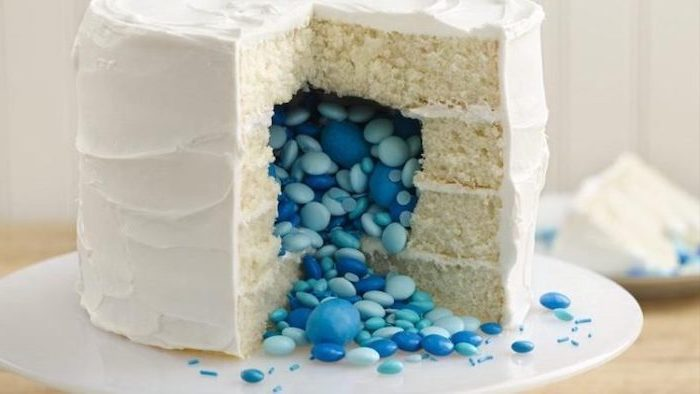 small cake, with white frosting, blue candy inside, gender reveal balloons, white cake stand