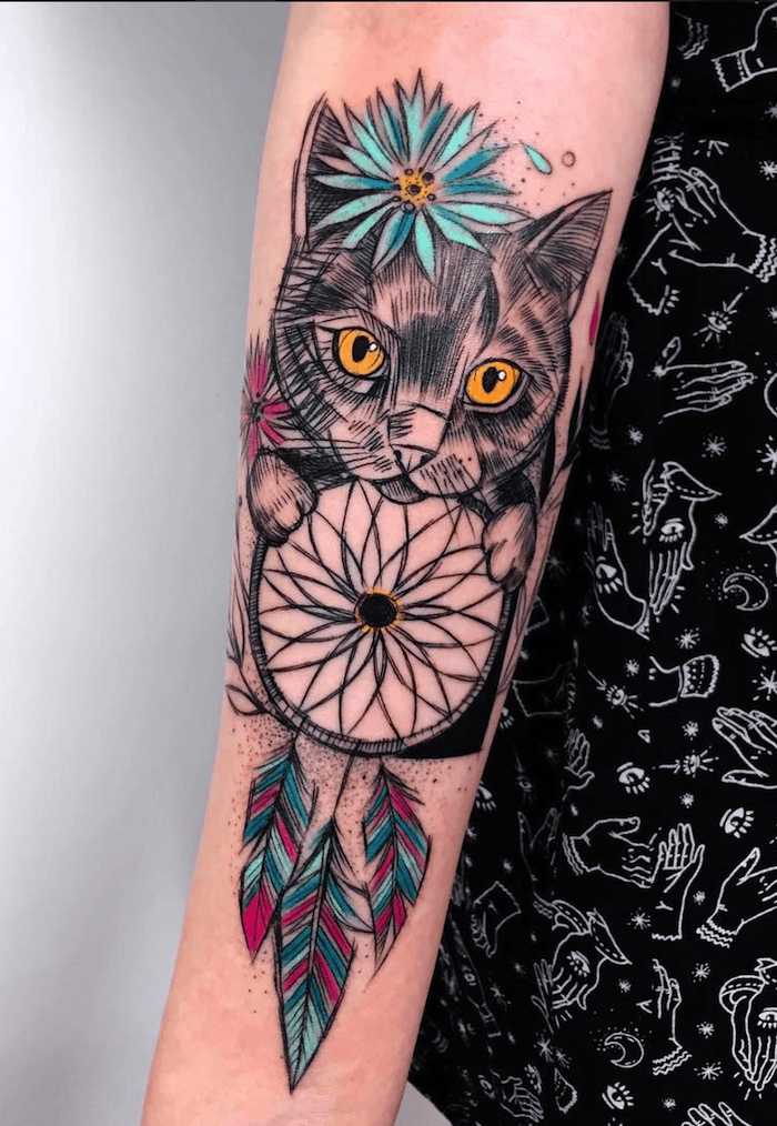 cat holding a dreamcatcher, dream catcher tattoo, colored tattoo, forearm tattoo, white background