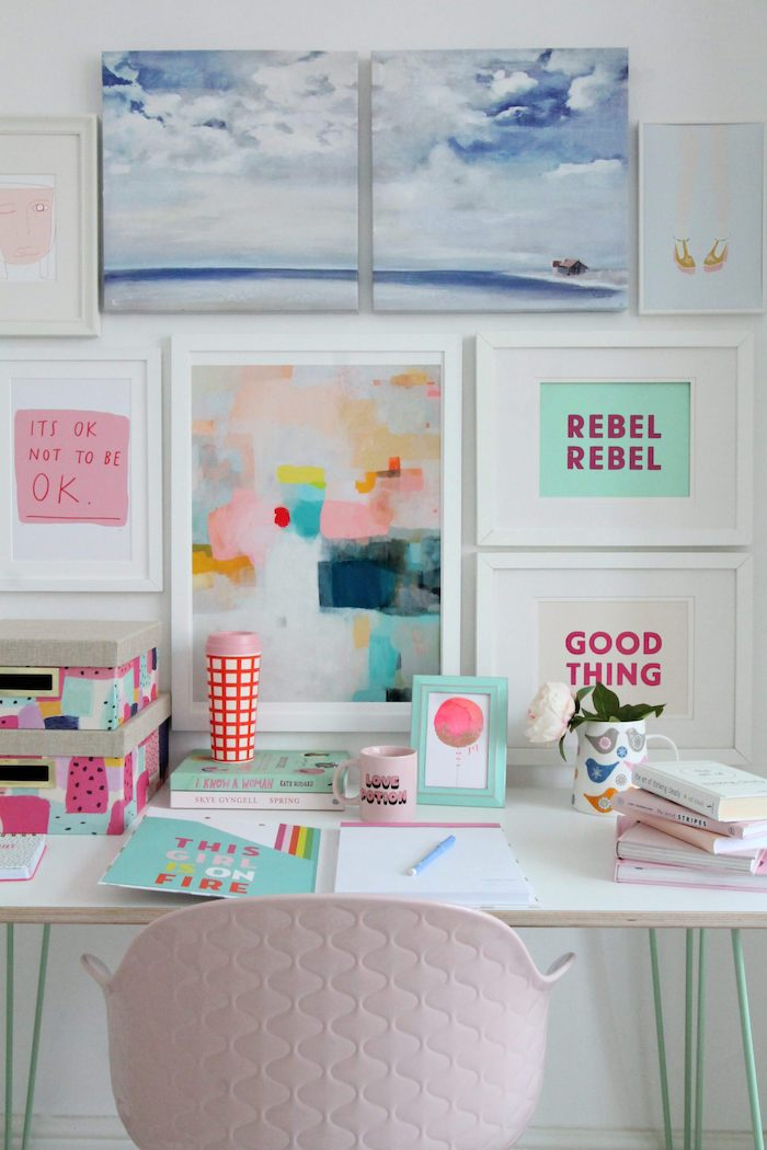 framed art, hanging on a white wall, office decor ideas, white desk, covered in books, pink chair