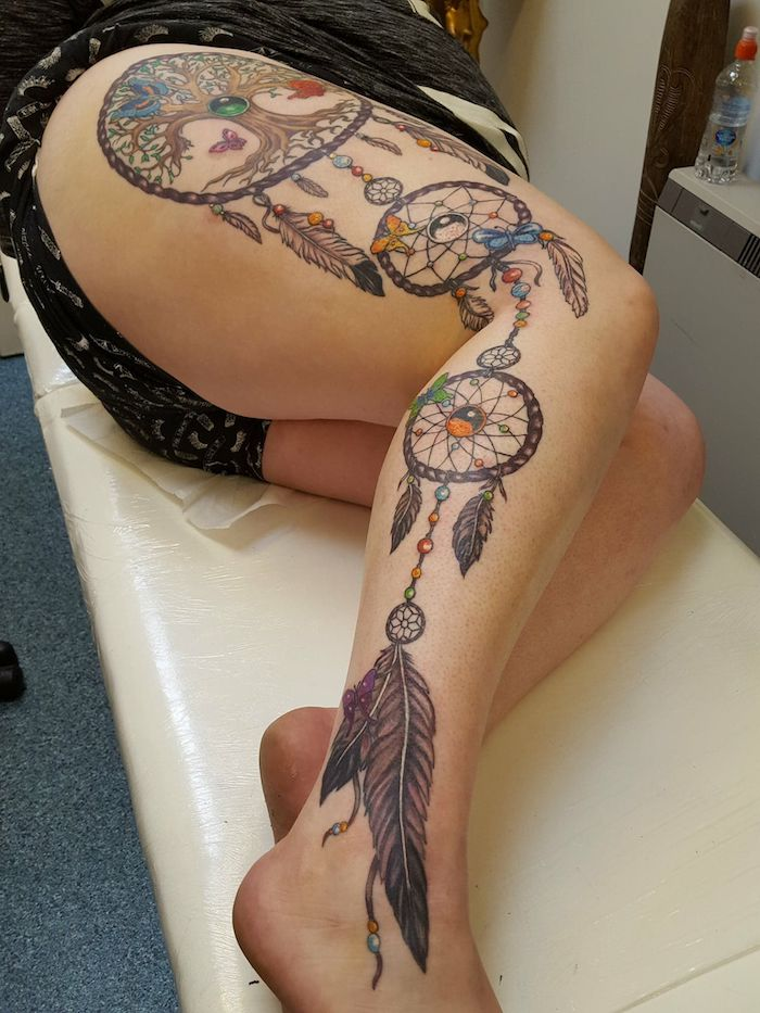 large leg tattoo, whole leg, small dreamcatcher tattoo, woman laying, on a white leather bed