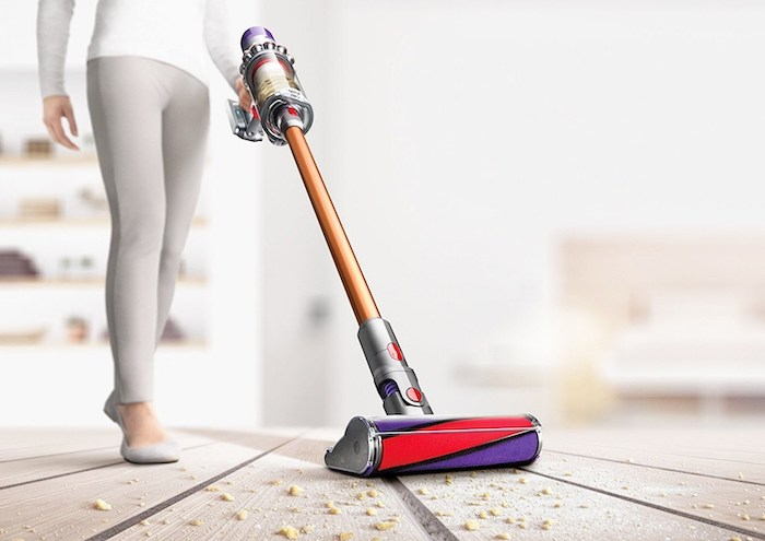 woman cleaning, wearing white blouse, gray trousers, wooden floor with breadcrumbs, best vacuum cleaner