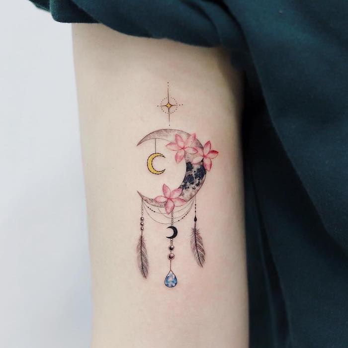 crescent moon, pink flowers, small dreamcatcher tattoo, back of arm tattoo, black shirt, white background