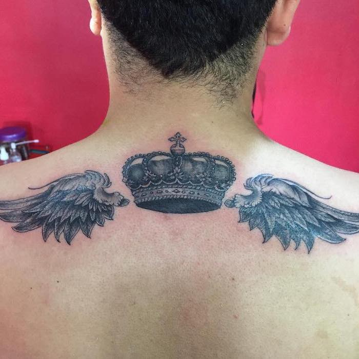 pink background, angel wings, crown in the middle, small angel wings tattoo, man with black hair