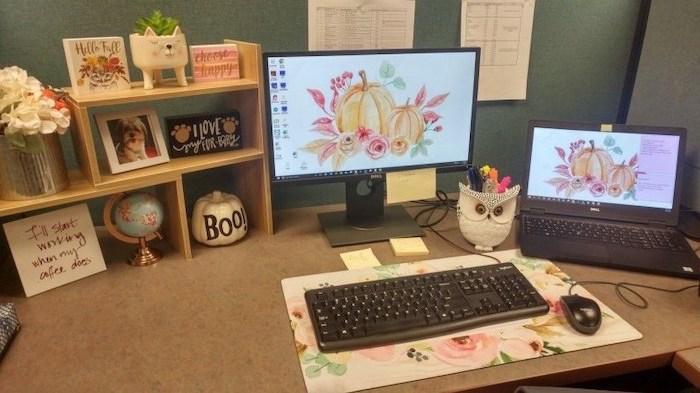 desktop computer and laptop, cubicle wallpaper, floral keyboard pad, wooden desk organiser, flower bouquet