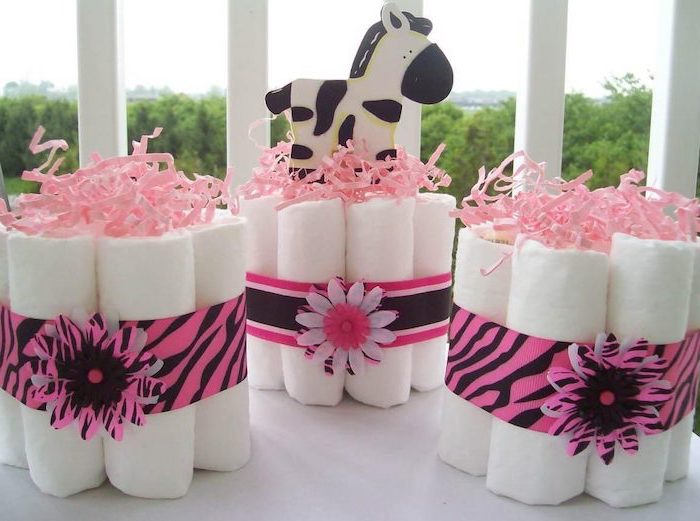 diapers arranges together, with a pink ribbon, girl baby shower, white table