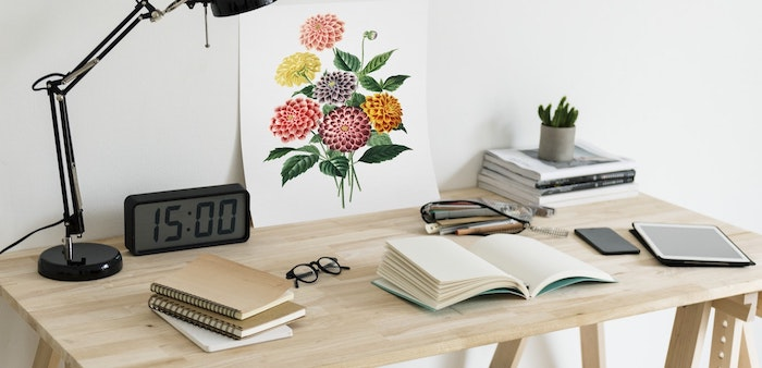 wooden desk, covered in books, digital clock, floral art, cubicle accessories, black lamp, white wall