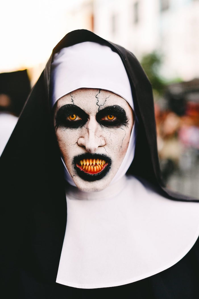 woman dressed as the nun, from the conjuring, halloween costumes, face make up, fake teeth, contact lenses