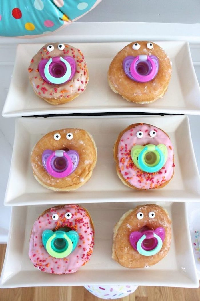 sprinkled donuts, with pacifiers, on white plates, dinosaur baby shower