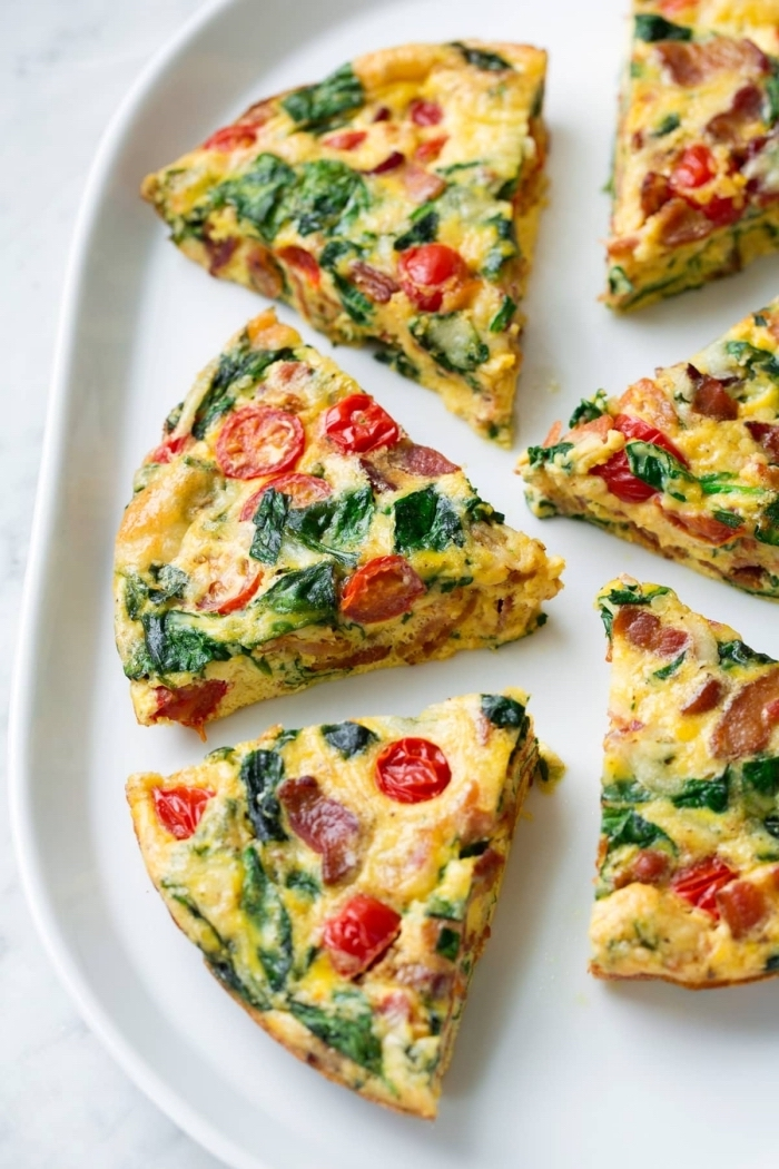 baked casserole, with spinach, cherry tomatoes, white plate, great breakfast ideas, marble countertop