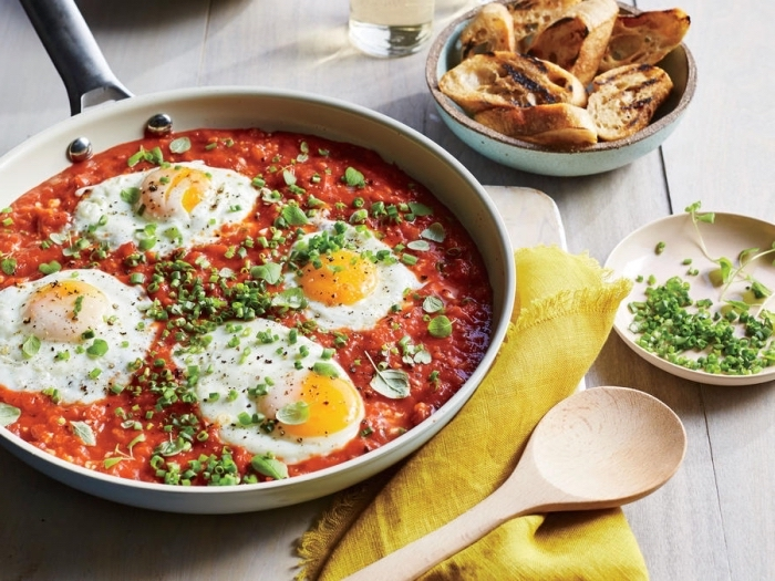 fried eggs, in tomato sauce, chives on top, breakfast brunch, wooden spatula, toasted bruschettas