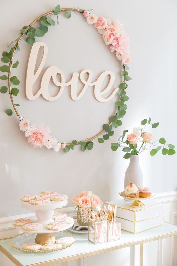 floral wreath, baby shower ideas, cake stand, cookies on it, small flower bouquets, love sign, white wooden table