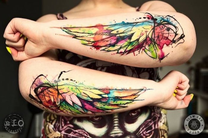 watercolor tattoo, angel and devil tattoo, forearm tattoos, on both hands, yellow nail polish