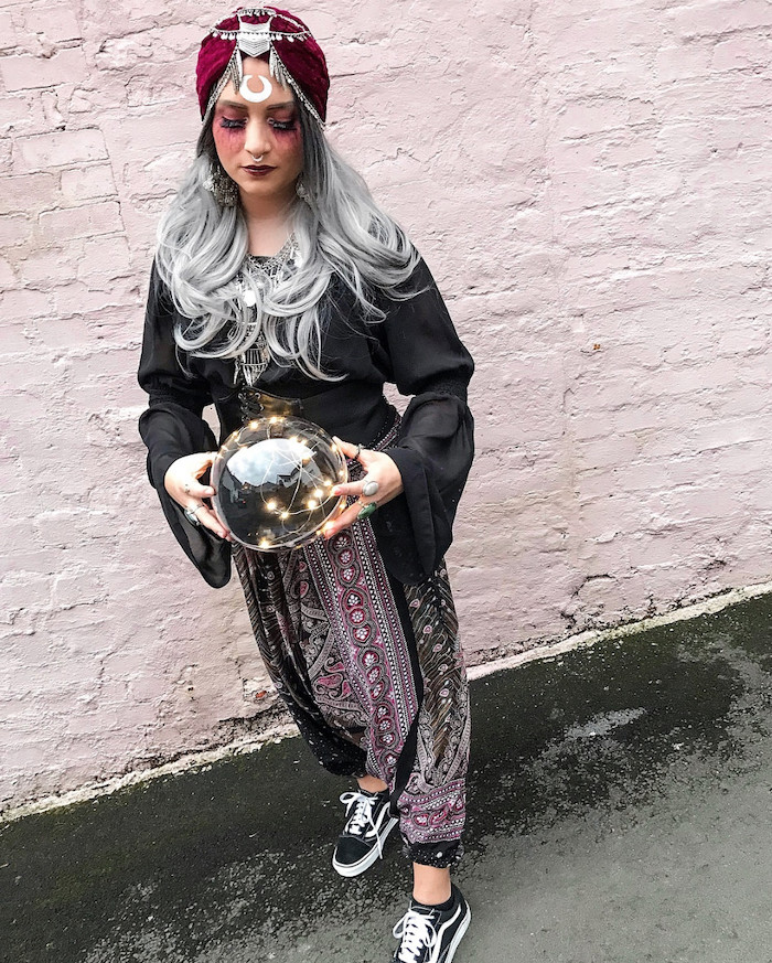 adult halloween costumes, woman with grey hair, dressed as a fortune teller, in front of a white brick wall