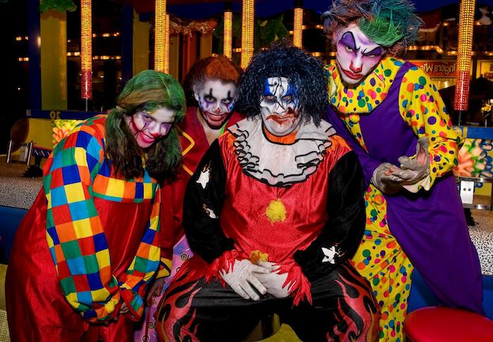 four people, dressed in clown costumes, adult halloween costumes, wearing clown make up