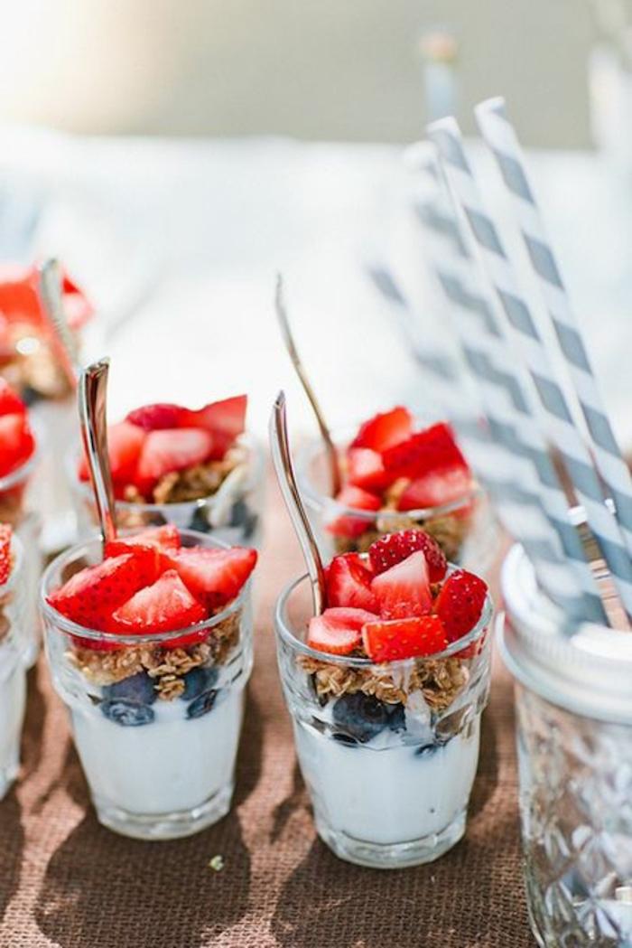 breakfast menu ideas, granola and yoghurt, blueberries and strawberries, silver spoons, paper straws