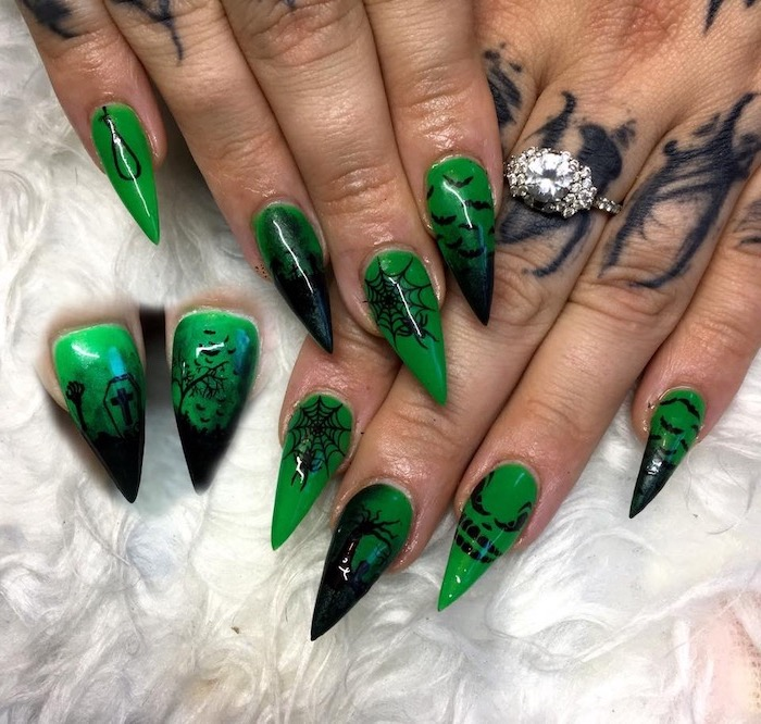 green nail polish, cute acrylic nail designs, black cemetery decorations, spider webs, trees and bats, long stiletto nails