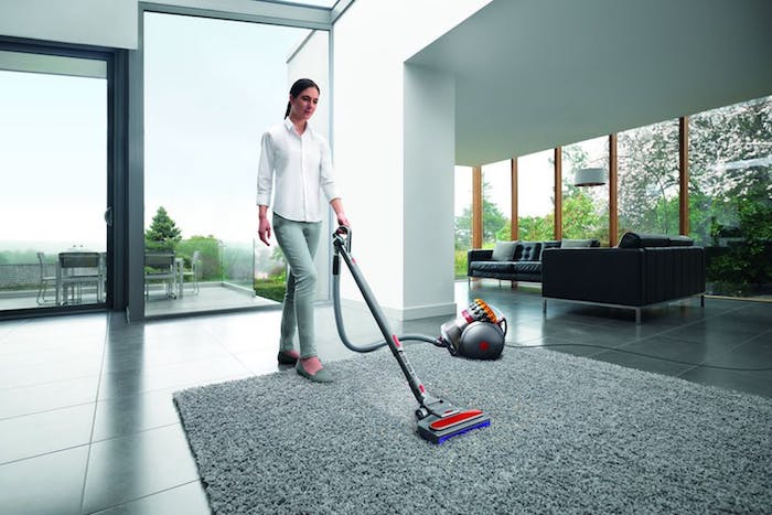 woman cleaning, wearing white shirt, grey trousers, best vacuum cleaner, gray carpet, tiled floor