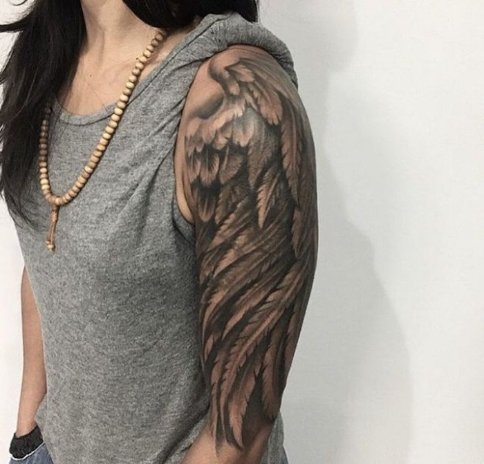 arm sleeve tattoo, angel wing, angel and devil tattoo, woman with black hair, grey top, wooden necklace