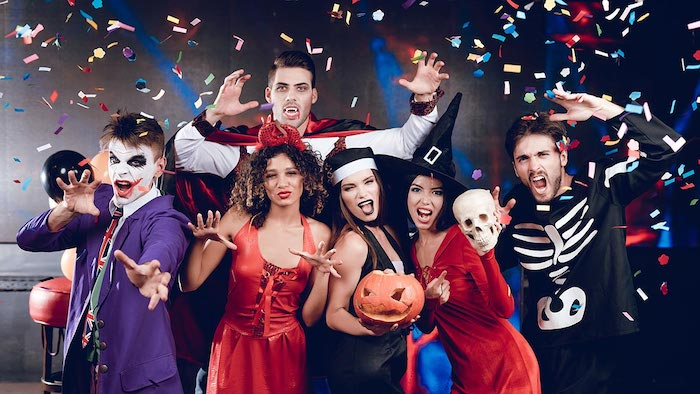 halloween costume ideas, group of people, dressed in different costumes, confetti flying around